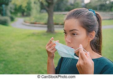 使用, 放, 面罩, 亞洲人, 外科, 女孩, 嚴肅, 臉, 婦女, coronavirus, 醫學, prevention., 等級, 覆蓋物