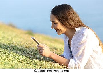 婦女, smartphone, 使用, 草, 躺, 愉快