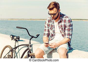 vacation., 握住運載工具, 接觸, 是, 年輕, 深思, 停留, 電話, 人坐, 欄杆, 自行車, 他的, 當時